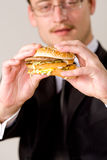 Hungry businessman eating hamburger Royalty Free Stock Images