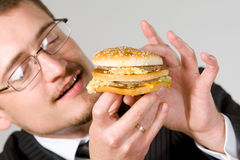 Hungry businessman eating hamburger Stock Photography