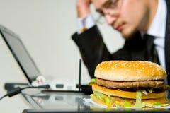 Hungry businessman eating hamburger Stock Photography