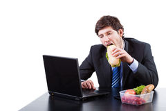 Hungry businessman eating a sadwich Royalty Free Stock Images