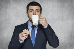 Hungry businessman eating a sandwich Royalty Free Stock Photography