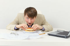 Hungry businessman eats tasty sandwich Stock Image