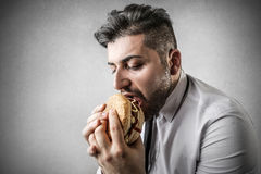 Hungry businessman during lunch break stock image