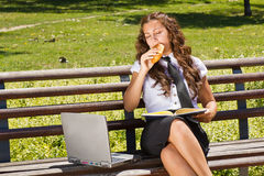 Hungry businesswoman in park Stock Images