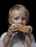 Hungry child eating bread. Poor hungry child eating bread royalty free stock photo