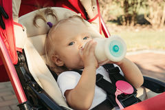 Hungry child eating from the pacifier bottle Stock Image