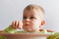 Hungry child eats lunch with big appetite. Cute boy eats pasta. Food strength Stock Images