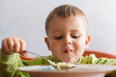 Hungry child eats lunch with big appetite. Cute boy eats pasta. Food strength Stock Image