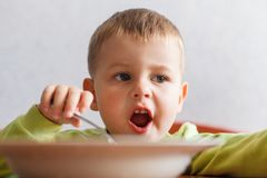 Hungry child eats lunch with big appetite. Cute boy eats pasta. Food strength Royalty Free Stock Photography