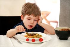 Free Hungry Child Sitting In Chair At Table In Kitchen And Eating With Spoon Of Cooked Peas With Tomato. Kids Meal And Healthy Food. Stock Photography - 145564982