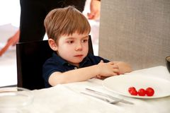 Free Hungry Child Sitting In Chair At Table In Kitchen And Waiting For Meal And Lunch. Boy Is Curious What He Will Get For Meal. Royalty Free Stock Photography - 145564757