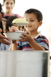 Hungry children in refugee camp. Distribution of humenitarian food Stock Image