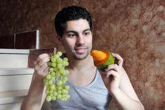 Hungry confused arab young man with mango fruit and grape Stock Photos