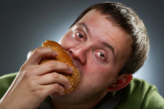 Hungry corpulent man eating white bread Stock Photo
