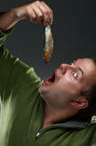 Hungry corpulent man staring at a fish. Hungry corpulent man with open mouth staring at a fish Royalty Free Stock Images