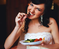 Hungry cute bride eating from plate Stock Photos