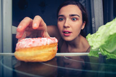 Hungry cute female reaches for donut at night near fridge Royalty Free Stock Photos
