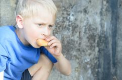 A hungry dirty boy greedily eats a crust of bread against the wall. A hungry dirty boy greedily eats a crust of bread against the wall Royalty Free Stock Photography