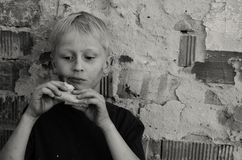 A hungry dirty boy greedily eats a crust of bread against the wall. Black and white. A hungry dirty boy greedily eats a crust of bread against the wall Royalty Free Stock Images