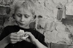A hungry dirty boy greedily eats a crust of bread against the wall. Black and white. A hungry dirty boy greedily eats a crust of bread against the wall Royalty Free Stock Photo