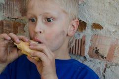 A hungry dirty boy greedily eats a crust of bread against the wall. A hungry dirty boy greedily eats a crust of bread against the wall Stock Images