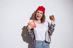 Hungry emotional lady holding fries and burger Royalty Free Stock Images