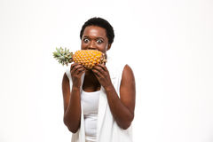 Hungry excited african american woman holding and biting fresh pineapple stock image