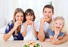 Hungry family eating burgers in the living room Royalty Free Stock Photos