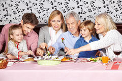 Hungry family reaching for food at. Dinner table at the same time Stock Photos