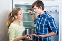 Hungry family standing near empty fridge Stock Photo