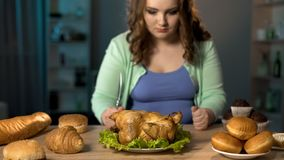 Hungry fat lady preparing to eat roast chicken, holding fork and knife in hands. Stock photo stock photos