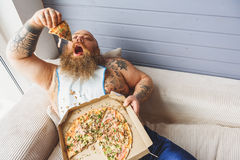 Hungry fat man eating unhealthy food Stock Image