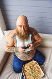 Hungry fat man holding joystick Royalty Free Stock Image