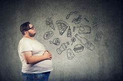 Hungry fat man thinking of junk food. Hungry fat lazy young man thinking of junk and fast food stock images