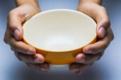 A hungry female holding an empty bowl. Stock Images