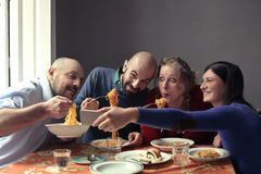 Hungry friends eating spaghetti Stock Images