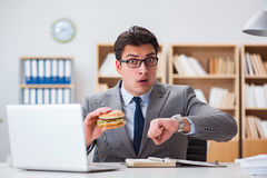 The hungry funny businessman eating junk food sandwich. Hungry funny businessman eating junk food sandwich Stock Photography