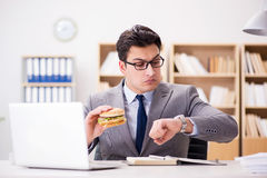The hungry funny businessman eating junk food sandwich Royalty Free Stock Images