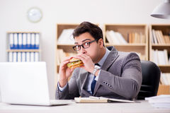 The hungry funny businessman eating junk food sandwich Stock Photo