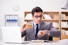The hungry funny businessman eating junk food sandwich Royalty Free Stock Photo