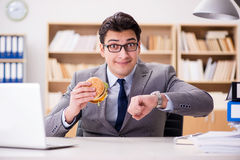 The hungry funny businessman eating junk food sandwich Stock Photography
