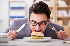 The hungry funny businessman eating junk food sandwich. Hungry funny businessman eating junk food sandwich Royalty Free Stock Photos