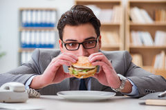 The hungry funny businessman eating junk food sandwich. Hungry funny businessman eating junk food sandwich Royalty Free Stock Images