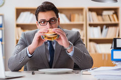 The hungry funny businessman eating junk food sandwich. Hungry funny businessman eating junk food sandwich Stock Photo