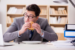 The hungry funny businessman eating junk food sandwich. Hungry funny businessman eating junk food sandwich Stock Photos