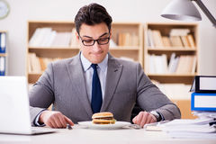 The hungry funny businessman eating junk food sandwich. Hungry funny businessman eating junk food sandwich Stock Image