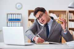 The hungry funny businessman eating junk food sandwich. Hungry funny businessman eating junk food sandwich Royalty Free Stock Photo