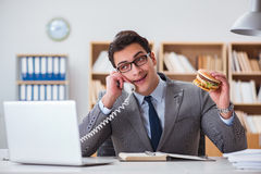 The hungry funny businessman eating junk food sandwich. Hungry funny businessman eating junk food sandwich Royalty Free Stock Photography