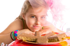 Hungry gesture blond kid girl in party chocolates Stock Images