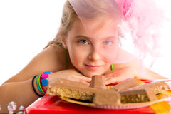Hungry gesture blond kid girl in party chocolates Royalty Free Stock Images